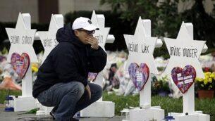 تصویر: در عکسی از ۲۹ اکتبر ۲۰۱۸، شخصی در مقابل «ستاره های داود» با نام کسانی که در تیراندازی مرگبار کنیسای «درخت زندگی» پیترزبورگ کشته شدند، درنگ کرده است. (AP Photo/Matt Rourke)