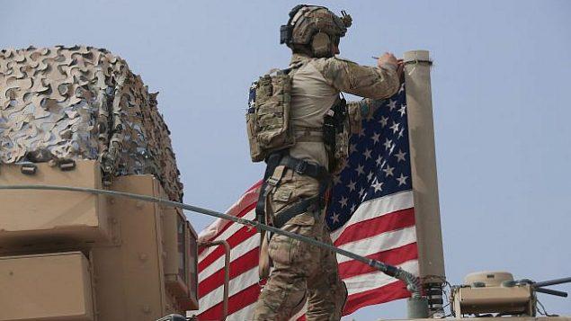 تصویر: ۲۰ اکتبر ۲۰۱۹، یک سرباز آمریکایی در نزدیکی شهر «تل تمار»، شمال سوریه، پرچم ایالات متحده را بر یک خودروی نظامی سوار میکند. رزمنده های تحت راهبری کوردها و نیروهای تحت رهبری ترکیه، روز یکشنبه، در شمال شرقی سوریه، در میان تلاشهایی که برای تخلیه کوردها از شهر مرزی تحت محاصره که اولین عقب نشینی تحت شروط آتش بسی است که به میانجیگری ایالات متحده صورت گرفت، بطور اتفاقی درگیر شدند.  (AP Photo/Baderkhan Ahmad)