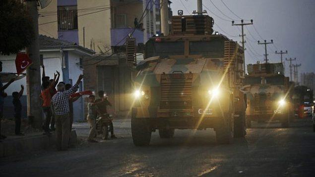 تصویر: اندکی پس از عملیات ترکیه در خاک سوریه شروع شد، ساکنان محلی با ورود قافله ای از خودروهای نیروی نظامی که از «آق قلعه»، استان «شأنلی اورفا» در جنوب غربی ترکیه، مرز ترکیه و سوریه میگذرد هلهله میکنند و کف میزنند، ۹ اکتبر ۲۰۱۹. (AP Photo/Lefteris Pitarakis)