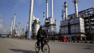 تصویر: یک کارگر نفت ایران با دوچرخه از نزدیکی پالایشگاه نفت در جنوب پایتخت ایران میگذرد، ۲۲ دسامبر ۲۰۱۴. (AP/Vahid Salemi)