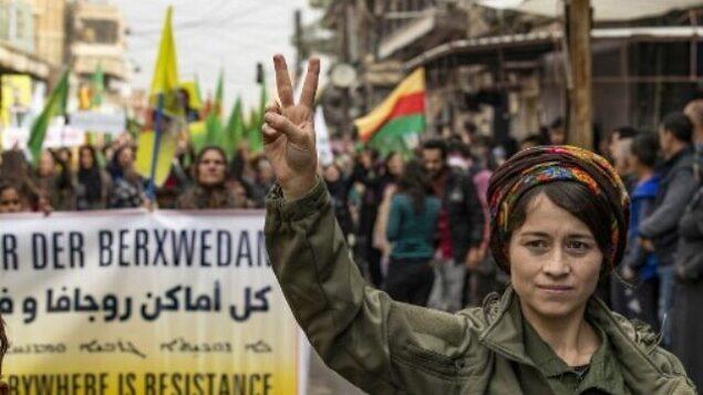 تصویر: یک عضو نیروهای امنیتی داخلی آسایش کورد، در تظاهرات علیه تهدید ترکیه در شهر قامشلی، شمالشرقی سوریه، که عملا پایتخت نیروهای اقلیت کورد در  سوریه بشمار می آید که درگیر جنگ اند، دو انگشت خود را به علامت پیروزی بالا برده است، ۲ نوامبر ۲۰۱۹. (Photo by Delil SOULEIMAN / AFP)