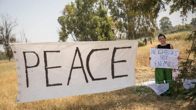 تصویر: علامت صلح در مزرعه ای نزدیک مرز غزه آویزان شده، همزمان هزاران فلسطینی در نزدیکی مرز اسرائیل و غزه در حال تظاهرات هستند، ۶ آوریل ۲۰۱۸. (Hadas Parush/Flash90)