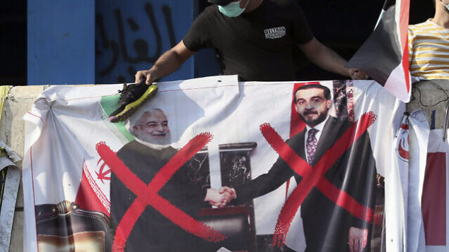 تصویر: یکی از معترضین در حال پرتاب کفش به پوستری از رهبر بازوی فرامرزی سپاه پاسداران انقلاب ایران، یا نیروی قدس، سرلشگر قاسم سلیمانی طی تظاهرات دامنه-دار ضدحکومتی در بغداد، عراق، ۳ نوامبر ۲۰۱۹.  (AP Photo)