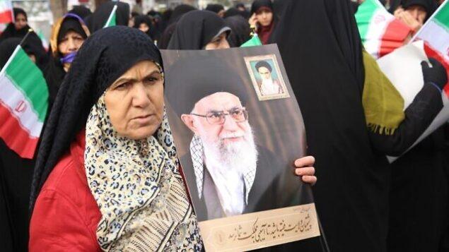 تصویر: حامیان دولت ایران حین تظاهرات در ۲۰ نوامبر ۲۰۱۹ در حمایت از مقامات جمهوری اسلامی و ولی فقیه، آیت الله علی خامنه ای (پوستر)، در شهر مرکزی اراک، جنوب غربی تهران، پایتخت، (STR / AFP)