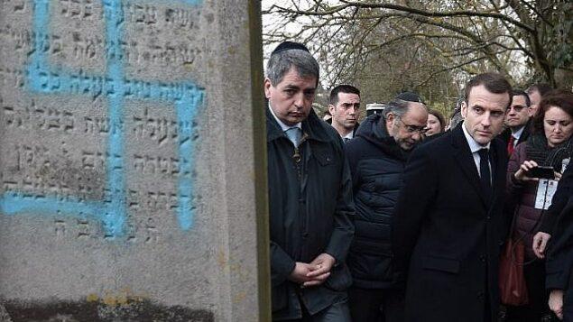 تزئینی: امانوئل مکرون رئیس جمهور فرانسه حین بازدید از آرامگاه یهودیان در «کواتزنهایم»، ۱۹ فوریه ۲۰۱۹، روزی که در سراسر کشور علیه خیزش تهاجمات یهودی ستیزی رژه برگزار شد، در حال تماشای سنگ گوری است که تخریب شده. (Frederick Florin/Pool/AFP)