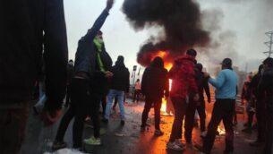 تصویر: تظاهرکنندگان ایرانی در اعتراضات علیه وضعیت اقتصادی و افزایش قیمت بنزین در تهران، دور اتوموبیلی که به آتش کشیده شده گرد آمده اند، ۱۶ نوامبر ۲۰۱۹. (AFP)