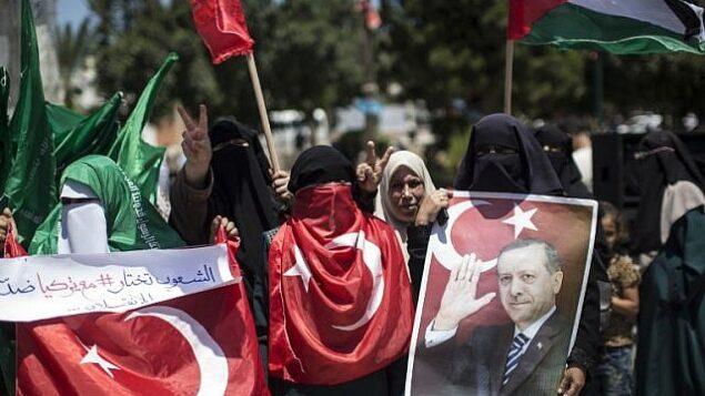 تصویر: حامیان فلسطینی جنبش حماس در تظاهراتی در شهر غزه، پرتره رجب طیب اردوغان رئیس جمهور ترکیه را در دست گرفته و علیه کودتای نافرجام نظامی در ترکیه شعار میدهند، ۱۷ ژوئیه ۲۰۱۶. (AFP/MAHMUD HAMS)