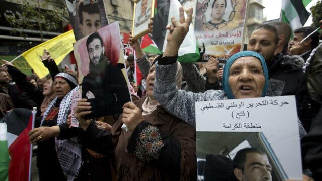 تصویر: خویشاوندان فلسطینی هایی که در اسرائیل زندانی اند، با تصاویر آنها در تظاهرات «روز زندانیان» در شهر رام الله از کرانه غربی، چهارشنبه، ۷ آوریل ۲۰۱۹. (AP Photo/Majdi Mohammed)