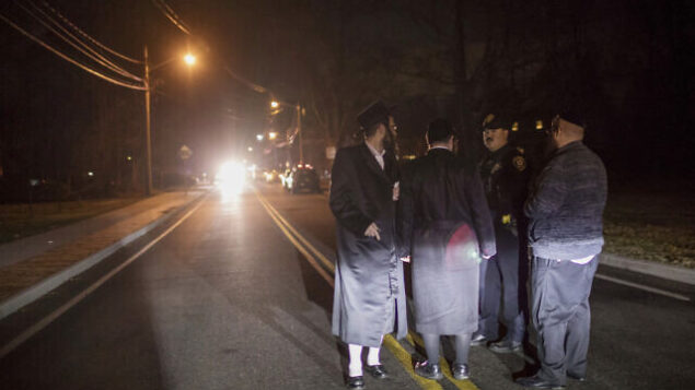 تصویر: مردان یهودی ارتدکس در حال گفتگو در خیابان فورشه، مانسی، نیویورک، یکشنبه، ۲۹ دسامبر ۲۰۱۹، پایین همان خیابانی که دیروقت شنبه شب در مراسم حنوکا کسی با چاقو به جمعیت حمله کرد. (AP/Allyse Pulliam)