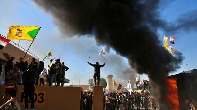 تصویر: معترضان در مقابل مجتمع سفارت ایالات متحده در بغداد، عراق، دست به ایجاد حریق در بنا زدند، ۳۱ دسامبر ۲۰۱۹. (Khalid Mohammed/AP)
