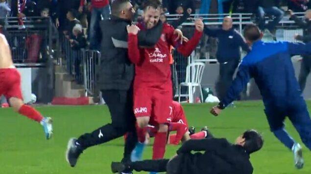 تصویر: «رئیف مسیکا»، از ام الفهم، در شادی پس از پیروزی بر تیم تل آویو، بهمراه مربی و بازیکنان، ۲۱ دسامبر ۲۰۱۹. (screen capture: Sport 5/IFL)