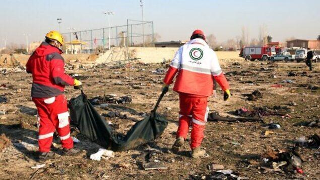 تصویر: پس از سرنگونی هواپیمای اوکراینی که ۸ ژانویه ۲۰۲۰ با ۱۷۶ مسافر در نزدیکی فرودگاه امام خمینی واقع در تهران، پایتخت ایران سقوط کرد و تمام مسافران آن کشته شدند، تیم امداد جسدی را از محل خارج میکند.  (AFP)