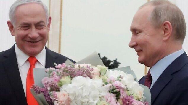تصویر: ولادیمیر پوتین رئیس جمهور روسیه، با دسته گل، در ملاقاتی که ایندو در کرملین مسکو داشتند، در کنار بنیامین نتانیاهو نخست وزیر ایستاده است، ۳۰ ژانویه ۲۰۲۰. (Maxim Shemetov/Pool/AFP)