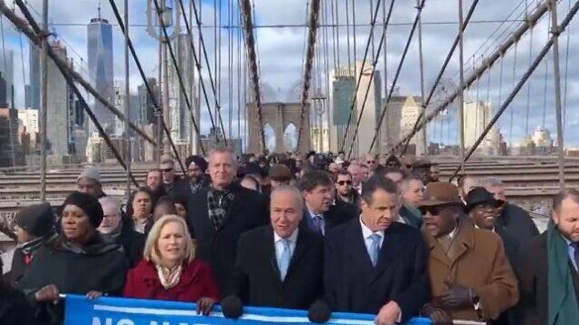 چهره های معتبر نیویورکی، از جمله شهردار بیل د بلاسیو، شهردار، سناتور چاک شومر، و فرماندار آندرو کومو در تظاهرات عظیم علیه یهودی ستیزی به سمت پل بروکلین میروند، ۵ ژانویه ۲۰۲۰. (Screenshot)