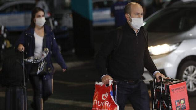 تصویر: مسافران برای جلوگیری از شیوع ویروس جدید کویید-۱۹ ویروط کرونا با ماسک به فرودگاه بین المللی سائو پولو در سائو پولوی برزیل وارد می شوند، چهارشنبه ۲۶ فوریه ۲۰۲۰. (AP/Andre Penner)