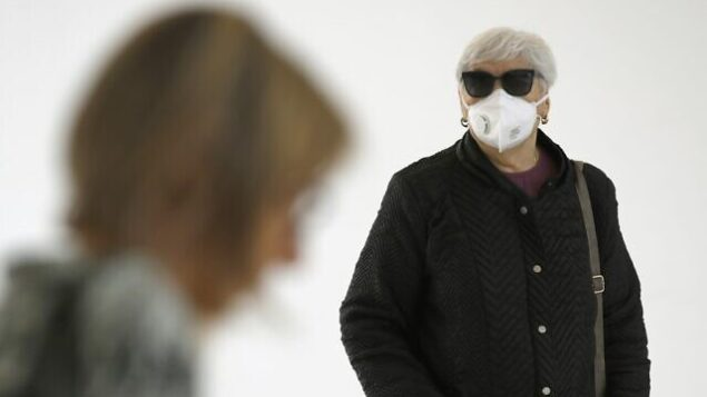 People wearing protective masks arrive at Samson Assuta Ashdod University Hospital on March 16, 2020 in the southern Israeli city of Ashdod, as the Jewish state introduces stringent measures to control the coronavirus pandemic. - Israel is grappling with 255 coronavirus cases amid an accelerating global Covid-19 pandemic. (Photo by JACK GUEZ / AFP)