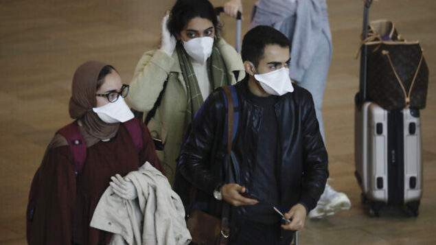 Passengers wearing masks to help protect against coronavirus arrive at the Ben Gurion Airport near Tel Aviv, Israel, Tuesday, March 10, 2020. Israel will quarantine anyone arriving from overseas for 14 days, a decision coming barely a month before Easter and Passover. According to the World  Health Organization, people with mild illness recover in about two weeks, while those with more severe illness may take three to six weeks to recover. (AP Photo/Ariel Schalit)