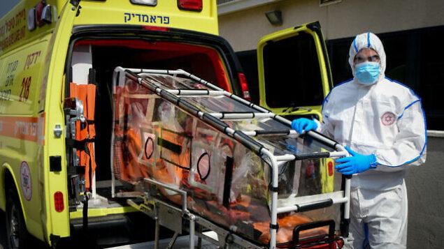 تصویر: یکی از کارکنان مگان دیوید آدوم با لباسهای محافظ برای ممانعت از ابتلا به ویروس کرونا بیرون مرکز تماس  اورژانس ویژه در «کیریات اونو»، ۲۶ فوریه ۲۰۲۰. (Flash90)