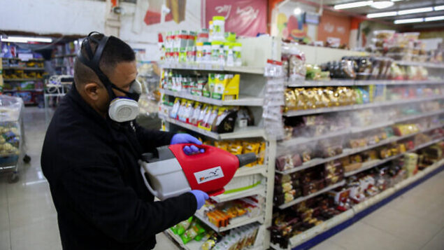 Workers disinfect Bar Kol Supermarket in the northern Israeli city of Tzfat, on March 16, 2020, as part of measures to prevent the spread of the Coronavirus. Photo by David Cohen/Flash90 *** Local Caption *** קורונה וירוס בר כל סופרמרקט עובדים בניין חיטוי