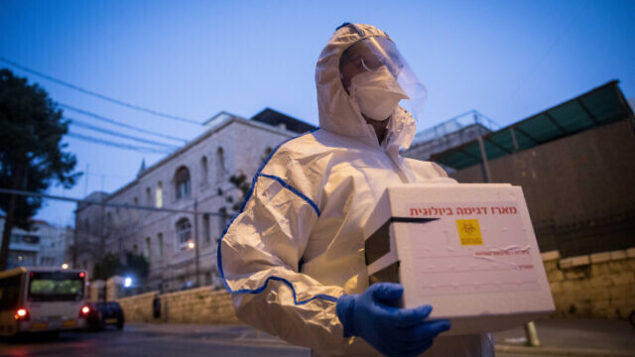 Magen David Adom worker wears protective clothing as a preventive measure against the coronavirus arrive to test a patient with symptoms of COVID-19 (coronavirus), in Jerusalem, March 16, 2020. Photo by Yonatan Sindel/Flash90 *** Local Caption *** ????? ?????? ???? ??? ?????? ????? ?????? ?????