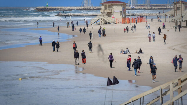 Israelis visit the beach in Tel Aviv on March 21, 2020. The Israeli governments has issued instructions to avoid public spaces, as the number of those infected by the Corona virus keeps growing. Photo by Avshalom Sassoni/Flash90 *** Local Caption *** תל אביב ריק  קורונה