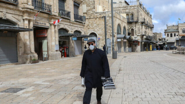 A man wearing a face mask for fear of the coronavirus walks near by the Jaffa Gate in the Old City of Jerusalem on March 21, 2020.  Israel's government approved additional measures to limit movement of citizens and banning gatherings of over 10 people to contain the covid 19 virus pandemic. Photo by Yossi Zamir/Flash90 *** Local Caption *** ????? ?????? ???? ??? ???????