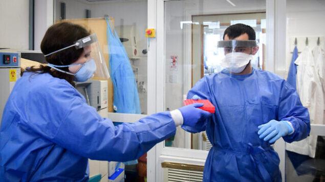 Medical team members at the Barzilay hospital, in the southern Israeli city of Ashkelon, wear protective gear, as they handle a Coronavirus test sample on March 29, 2020. Photo by Flash90 *** Local Caption *** ÷åøåðä åéøåñ îâéôä  öååú øôåàé äöìä áãé÷åú ðùàéí àù÷ìåï áøæéìàé