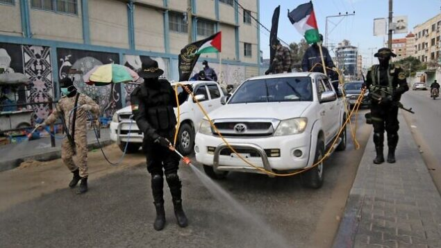 Members of the Palestinian Islamic Jihad's armed wing, the Al-Quds Brigades, spray disinfectant in the streets of Rafah  in the southern Gaza Strip, on March 26, 2020, during a campaign aimed at slowing down the spread of the novel coronavirus. (Photo by SAID KHATIB / AFP)