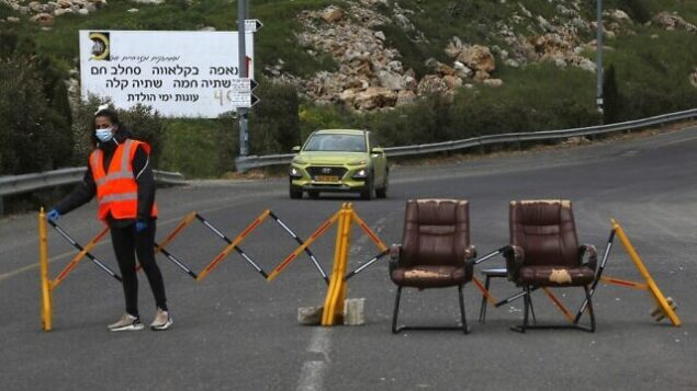 A woman stands next to a makeshift checkpoint, part of a community safety initiative in the Druze village of Majdal Shams in the Israel-annexed Golan Heights on April 9, 2020, amid the novel coronavirus epidemic. (Photo by JALAA MAREY / AFP)