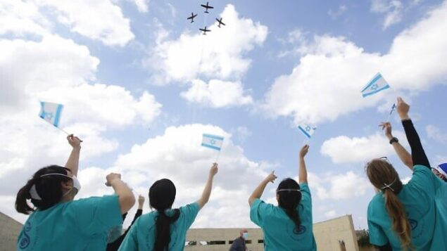 Israeli medical team of Sheba Medical Center at Tel HaShomer, wave national flags as the Israeli Air Force (IAF) fly over the hospital during Israel's Independence day (Yom Ha'atzmaut) celebrations amid the COVID-19 pandemic, in Ramat Gan on April 29, 2020. - Israel celebrates its 72nd anniversary of the declaration of independence in 1948. The annual aviation performance over Israeli beaches was cancelled and made into a solidarity flyover Israeli hospitals during a national closure due to the coronavirus disease (COVID-19) pandemic. (Photo by JACK GUEZ / AFP)
