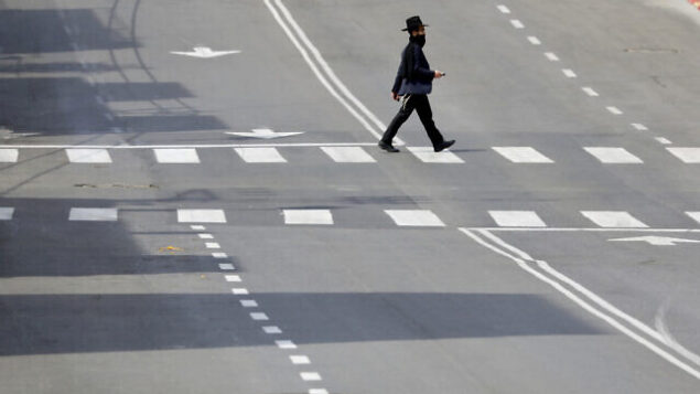 An Ultra orthodox man cross a main deserted street because of the government's measures to help stop the spread of the coronavirus in the orthodox city of Bnei Brak, a Tel Aviv suburb, Israel, Thursday, April 2, 2020. On Wednesday, Netanyahu ordered a police cordon around the largely ultra-Orthodox city of Bnei Brak, east of Tel Aviv, to limit movement to and from the city. Bnei Brak has the second highest number of coronavirus cases in Israel. (AP Photo/Ariel Schalit)