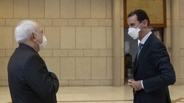 In this photo released by the Syrian official news agency SANA, Syrian President Bashar Assad, right, wears a mask to help protect from the coronavirus, as he speaks with Iranian Foreign Minister Mohammad Javad Zarif, who also wore a mask and gloves, in Damascus, Syria, Monday, April. 20, 2020. (SANA via AP)