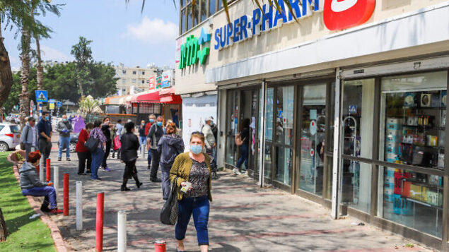 People wear protective face masks as they walk in Lod on April 12, 2020. The government ordered on a partial lockdown, in order to prevent the spread of the Coronavirus Photo by Yossi Aloni/Flash90 *** Local Caption ***