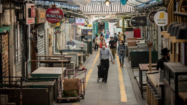 People shop for food at the Mahane Yehuda Market in Jerusalem on April 16, 2020. Photo by Yonatan Sindel/Flash90 *** Local Caption *** ?????? ????? ????? ??? ???? ?????