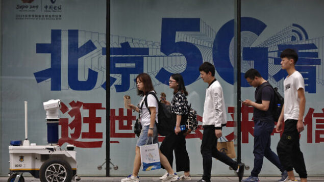 """People walk toward a police robot mounted with surveillance cameras patrol past a 5G network advertisement at a shopping district in Beijing, Wednesday, May 15, 2019. U.S. officials listed $300 billion more of Chinese goods for possible tariff hikes while Beijing vowed Tuesday to """"fight to the finish"""" in an escalating trade battle that is fueling fears about damage to global economic growth. (AP Photo/Andy Wong)"""