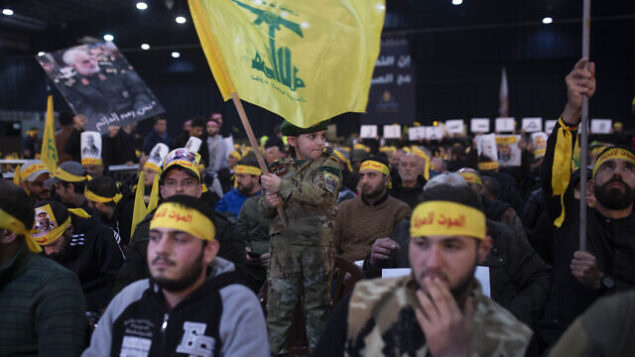 A child in tiny military fatigues waves the Hezbollah flag as supporters of the group's leader Sayyed Hassan Nasrallah wait for his televised speech in a southern suburb of Beirut, Lebanon, Sunday, Jan. 5, 2020 following the U.S. airstrike in Iraq that killed Iranian Revolutionary Guard Gen. Qassem Soleimani. (AP Photo/Maya Alleruzzo)