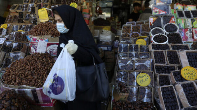 A woman wearing a protective face mask and gloves to help prevent the spread of the coronavirus carries her purchases as she leaves a store which sells dates, a favorite fruit for the Muslim holy fasting month of Ramadan, in southern Tehran, Iran, Monday, April 27, 2020. In Iran, the country that is hit worst in the Middle East by the coronavirus, all religious gathering, congregational prayers and communal Iftar servings, a meal eaten at sunset to break the fast, remain forbidden in the Ramadan and also holy shrines and religious centers also continue to be closed until at least May 4. (AP Photo/Vahid Salemi)