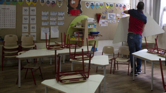 An Israeli parent helps prepare a classroom for the reopening of an elementary school in Tel Aviv, Israel, Thursday, April 30, 2020. Israel is considering reopening some elementary school classes starting Sunday. (AP Photo/Sebastian Scheiner)
