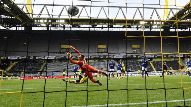 Dortmund's Raphael Guerreiro scores the his side's 4th goal against Schalke's goalkeeper Markus Schubert during the German Bundesliga soccer match between Borussia Dortmund and Schalke 04 in Dortmund, Germany, Saturday, May 16, 2020. The German Bundesliga becomes the world's first major soccer league to resume after a two-month suspension because of the coronavirus pandemic. (AP Photo/Martin Meissner, Pool)