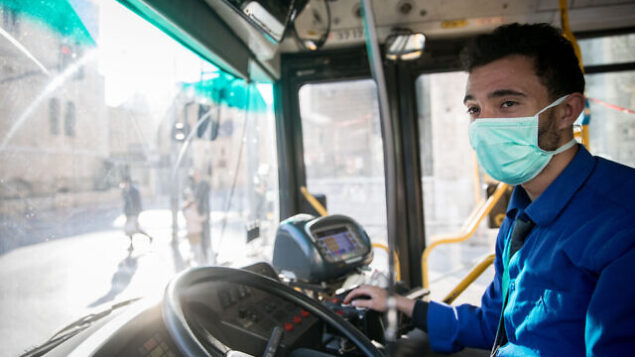 A bus driver sits in a bus and wears a face mask for fear of the coronavirus in downtown Jerusalem, March 16, 2020. Photo by Yonatan Sindel/Flash90 *** Local Caption *** וירוס קורונה מגפה סין ירושלים אוטובוס נהג