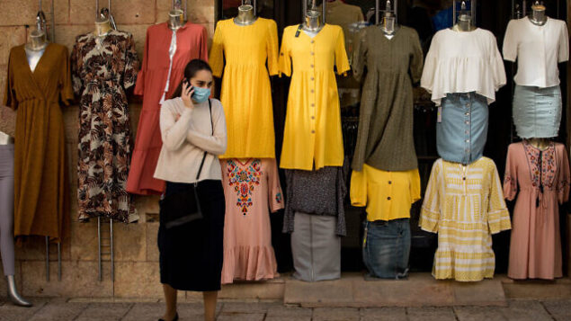 A woman wearing a protective face mask walks past a clothes shop in Jerusalem on April 26, 2020. Photo by Nati Shohat/Flash90