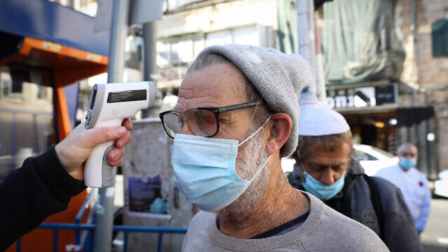 A man checks the temperature of a customer to identify if he have fever at the entrance to the Mahane Yehuda market in Jerusalem, which have been reopened according to the new government orders, May 7, 2020. Photo by Olivier Fitoussi/Flash90 *** Local Caption *** הפגנה שוק מחנה יהודה ירושלים כלכלה