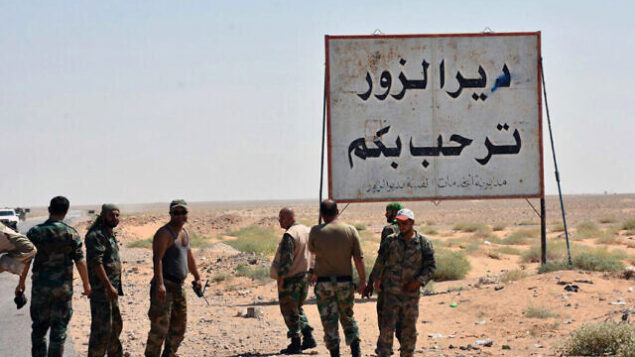 """FILE - This file photo released Sept. 3, 2017, by the Syrian official news agency SANA, shows Syrian troops and pro-government gunmen standing next to a sign in Arabic which reads, """"Deir el-Zour welcomes you,"""" in the eastern city of Deir el-Zour, Syria. As U.S.-allied fighters hurtle down the eastern banks of the Euphrates River, a showdown could ensue between the U.S. and Russia, whose allies are racing to take over the same strategic oil-rich territory from the Islamic State group. (SANA via AP, File)"""