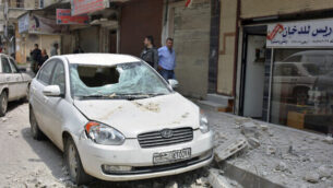 In this photo released by the Syrian official news agency SANA, people stand near a car that was damaged due to flying debris from a Syrian military base housing a weapons warehouse, in the country's central province of Homs, Syria, Friday, May 1, 2020. Explosions rocked a Syrian military base housing a weapons warehouse Friday in the country's central Homs province, and a local official said the cause was not immediately clear. (SANA via AP)
