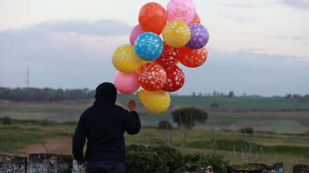 Young Palestinian men prepare a flammable object to be flown toward Israel, near the Israel-Gaza border east of Al-Bureij refugee camp in the central Gaza Strip, January 22, 2020. Photo by Ail Ahmed/Flash90  *** Local Caption *** ôìñèéðéí øöåòú òæä âáåì éùøàì áìåðéí áìåðé úáòøä