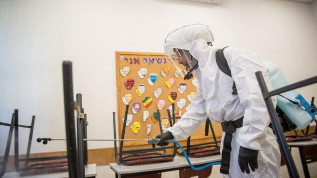 Cleaning workers disinfect a classroom at the Gymnasia Rehavia high school in Jerusalem on June 3, 2020. Photo by Yonatan Sindel/Flash90 *** Local Caption *** קורונה וירוס ניקוי עובדים בניין חיטוי גימנסיה גמנסיה בית ספר