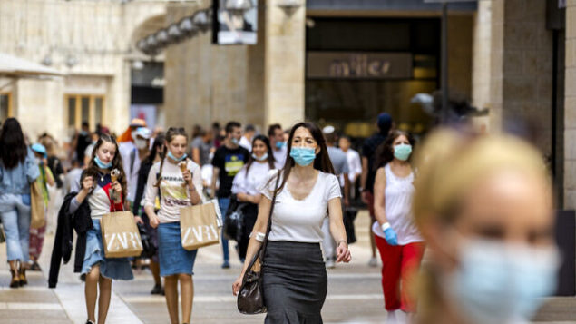 Jerusalemites walk and shopp at the Mamilla Mall near Jerusalem's Old City on June 04, 2020. Shops are allowed to reopen with strict measures such as limiting the number of customers on the premises and wearing face masks and temperature measurment of all customers at the entrance. Photo by Olivier Fitoussi/Flash90 *** Local Caption *** וירוס קורונה מגפה ירושלים העיר העתיקה ממילא