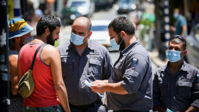 Inspectors talk to people who are not wearing face mask in the northern Israeli city of Tzfat, June 15, 2020. Photo by David Cohen/Flash90 *** Local Caption *** ?????? ???? ??? ?????