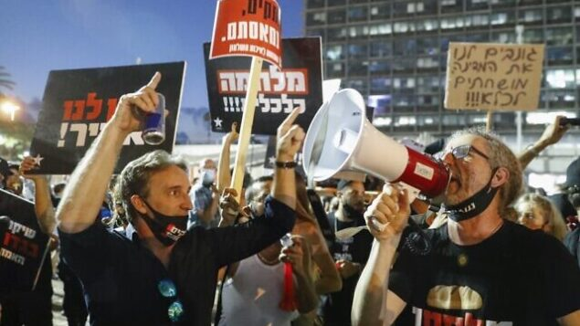 Israelis lift placards and chant slogans during a demonstration in Rabin Square in the central coastal city of Tel Aviv, on July 11, 2020, to protest the government's abandonment of the country's self-employed and other sectors after forcing their businesses to close under COVID-19 regulations, according to the organizers. (Photo by Jack GUEZ / AFP)