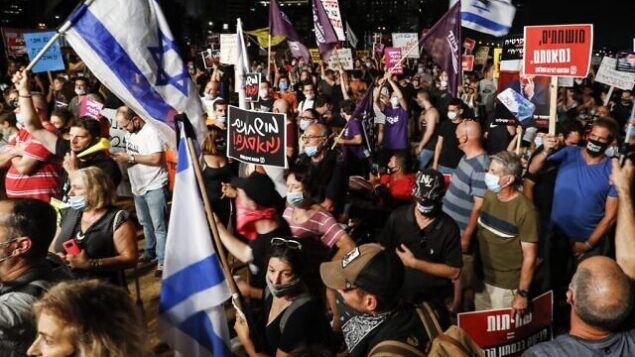 Anti-government protesters, clad in masks due to the COVID-19 coronavirus pandemic, gather with Israeli flags and signs during a demonstration in Charles Clore Park in the Mediterranean coastal city of Tel Aviv on July 18, 2020, against the Israeli government for broken promises made during the novel coronavirus pandemic. (Photo by Jack GUEZ / AFP)